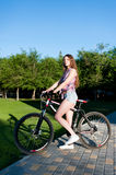 Girl sitting on bicycle Stock Images