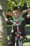 Girl (7-9) sitting on bicycle beside tree in garden, leaning forwards, smiling, front view, portrait Royalty Free Stock Image