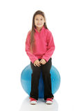 Girl sitting on a big ball Stock Images