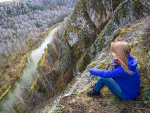 A girl sitting on the big gray rock among the mountains near the river. Blue river between the rocks and a girl sitting on the stone. A girl looking at the Stock Photos