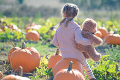 Girl sitting on a big pumpkin hugging teddy bear Royalty Free Stock Image