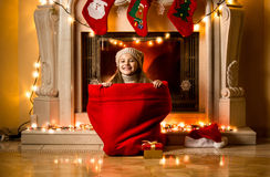 Girl sitting in big red sack at room decorated for Christmas Stock Photo