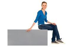 Girl sitting on a blank sign Royalty Free Stock Image