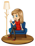 A girl sitting at the blue couch Royalty Free Stock Photos