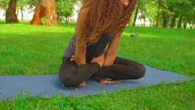 Young woman doing asana slow motion. Girl sitting on the blue yoga mat in park lady with long curly hair trains outdoor. nature landscape with green grass and stock footage