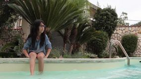Girl Sitting On The Board Of The Swimming Pool stock footage