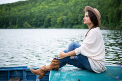 Girl sitting in a boat on a lake. Pretty girl sitting in a boat on a lake Royalty Free Stock Image