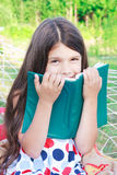 Girl sitting with book on hammock outdoor Royalty Free Stock Image