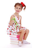 Girl sitting on books Stock Photography