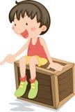 A Girl Sitting on a Box Stock Photos