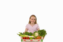 Girl sitting with box of vegetables, smiling, portrait, cut out Royalty Free Stock Photo