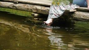 Girl sitting on the bridge and dangled his legs in the water splashing sun glare stock video footage