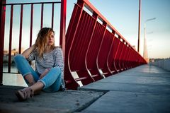 The girl is sitting on a bridge in jeans and a striped shirt royalty free stock photo