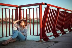 The girl is sitting on a bridge in jeans and a striped shirt stock photography