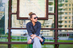 Girl sitting on a bus stop bench Royalty Free Stock Photos
