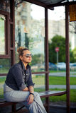 Girl sitting at the bus stop Stock Photo
