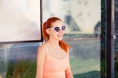 The girl sitting at the bus stop in sunglasses waiting for the bus stock photos