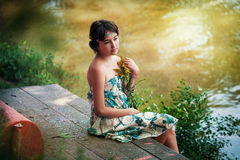 Girl Sitting By A Lake Stock Image