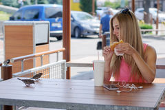 Girl sitting in cafe and feeding the birds Stock Photography