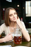 Girl sitting in the cafe with a glass of beer Royalty Free Stock Photography