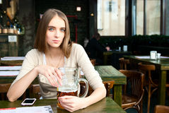 Girl sitting in the cafe with a glass of beer Stock Images