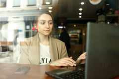 Girl sitting at a cafe table with a laptop computer Stock Images