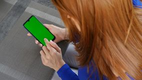 Girl sitting in a cafe and using mobile phone with green screen. Close up. Girl sitting in a cafe and using mobile phone with green screen stock video