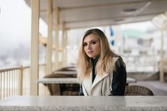 A girl is sitting in a cafe and waiting for someone. Very beautiful girl in the afternoon one sits in a bright cafe and waits for someone Stock Image