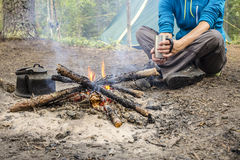 Girl sitting while camping near the fire heated and drink hot tea Stock Photo