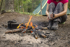 Girl sitting while camping near the fire heated and drink hot tea Royalty Free Stock Photos