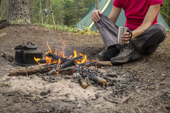 Girl sitting while camping near the fire heated and drink hot tea Royalty Free Stock Images