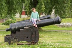 The girl is sitting on a cannon Royalty Free Stock Images