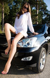 Girl sitting on car Stock Image