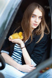 Girl sitting in the car and keeps the duckling Stock Photo