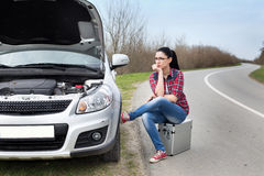 Girl sitting beside car with opened hood. Young woman sitting on the suitcase beside stopped car with opened hood by the road Stock Photos