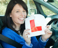 A girl sitting in a car tearing a L-sign Stock Photo