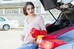 Girl is sitting in car trunk with flowers Royalty Free Stock Photography