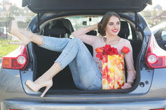 Girl is sitting in car trunk with gift package Royalty Free Stock Photography