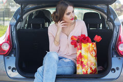 Girl is sitting in car trunk with gift  package Stock Photos