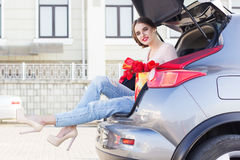 Girl is sitting in car trunk with red flowers Stock Photos