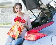Girl is sitting in car trunk with red flowers Stock Images