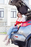 Girl is sitting in car trunk with red tulips Stock Photo