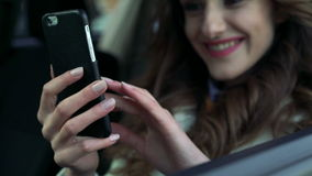 Girl sitting in the car using phone, smiling and looking through the window stock footage