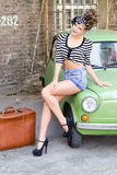 Girl sitting on car. Young pin up girl sitting on car Royalty Free Stock Photography
