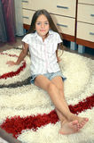 Girl sitting on a carpet Royalty Free Stock Photo