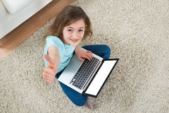 Girl Sitting On Carpet With Laptop royalty free stock image