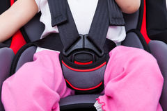 Girl sitting at carseat and fasten seat belt. Image of little asian (thai) girl sitting at carseat and fasten seat belt. Concept about the safety of traveling by Royalty Free Stock Photos