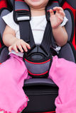 Girl sitting at carseat and fasten seat belt. Image of little asian (thai) girl sitting at carseat and fasten seat belt. Concept about the safety of traveling by Royalty Free Stock Photo