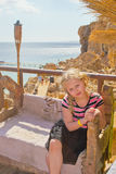 Girl sitting on a carved wooden bench. Girl sitting on a high rocky shore on the sea background stock images