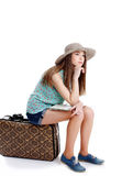 Girl sitting on the case going on a journey, white background Stock Photos